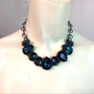 Deep blue gemstones encased in dark silver patina